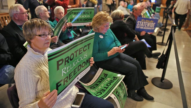 Diana Freeman and others hold signs for religious freedom outside the Senate chambers during testimony Jan. 27 on Senate Bill 344.
