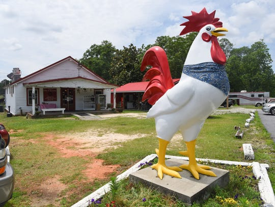 A large statue of a chicken is near the parking lot