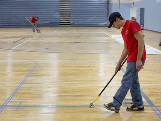 Aaron Heacock works on refinishing and painting the gym floor Tuesday, July 21, 2015 at Yale High School. Voters will be asked to renew the 1 mill sinking fund on August 4, which will generate approximately $1.8 million over five years.