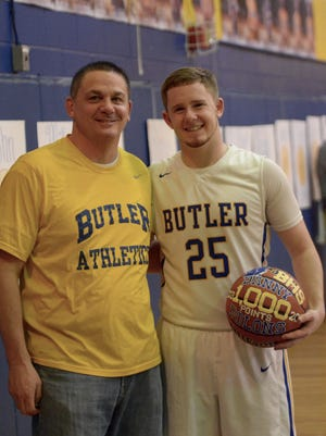 Butler senior basketball player Danny Polons, right, was presented with a commemorative ball by athletic director Dave Doty shortly after scoring his 1,000th career point in Thursday's home loss to Kinnelon.