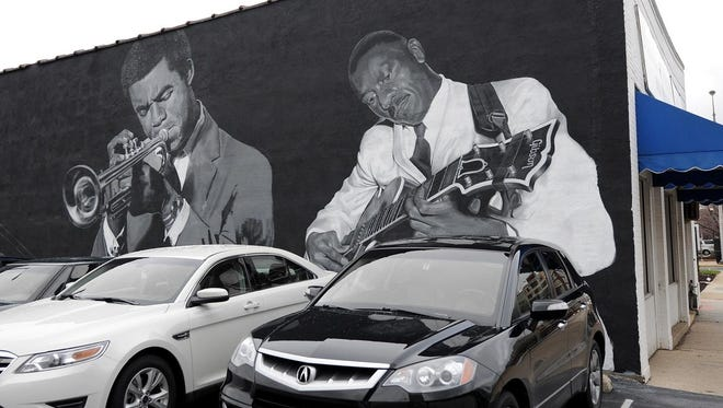 In this 2011 photo, a mural of Indianapolis jazz greats is still in progress on the side of the Musicians' Repair & Sales shop, 332 N. Capitol Ave. Images of Freddie Hubbard, left, and Wes Montgomery are seen.