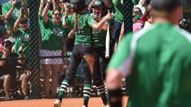 Vivian Ponn (center) celebrates scoring in the first inning with temmate Jessica Wilson during their 7-1 victory over Niceville on Saturday in the Class 7A state final at Historic Dodgertown. The Green Wave captured the first state title in program history. CQ Vivian Ponn,  Jessica Wilson