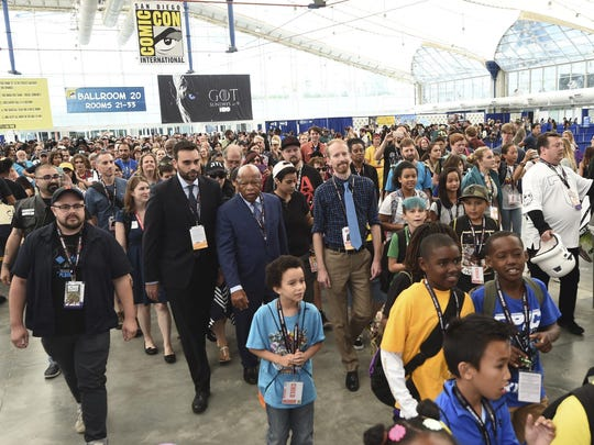 """Andrew Aydin, from center left, Rep. John Lewis, D-Ga., Nate Powell and fans participate in a demonstration following a panel for """"MARCH"""" on day three of Comic-Con International on Saturday, July 22, 2017, in San Diego."""