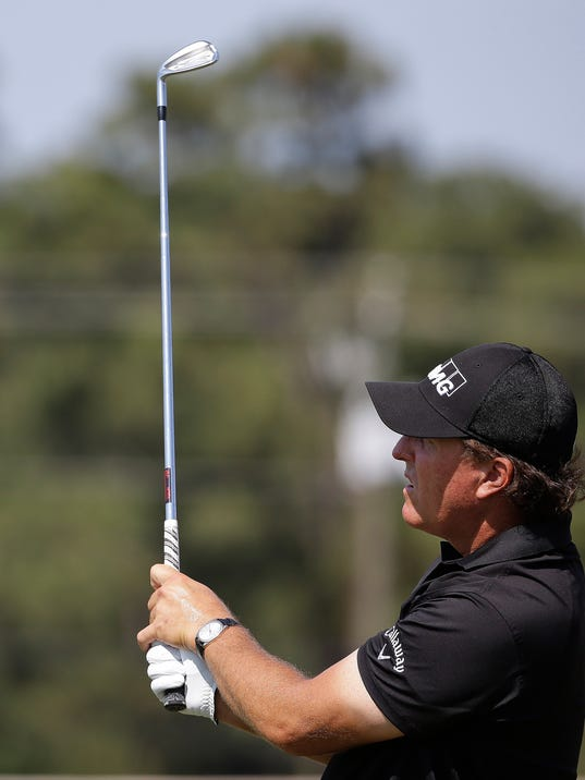 Phil Mickelson views his shot on the driving range before a practice round for the U.S. Open golf tournament in Pinehurst, N.C., Wednesday, June 11, 2014. The tournament starts Thursday. (AP Photo/David Goldman)
