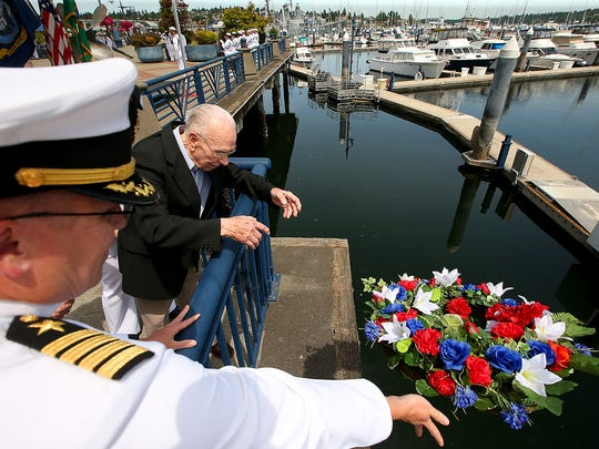 World War II veteran Roy Ellefson, of Port Angeles, and Naval Base Kitsap commanding officer Capt. Alan Schrader drop a wreath into Sinclair Inlet during a ceremony marking the 75th anniversary of the the Battle of Midway. Poulsbo resident and WWII veteran Kenneth Jensen also helped toss the wreath into the water.