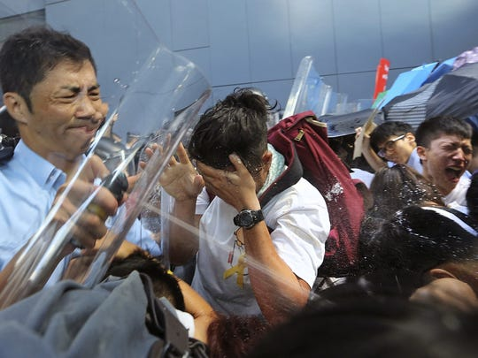 Riot police pepper-spray pro-democracy activists who forced their way into Hong Kong government headquarters during a demonstration in Hong Kong, on Saturday, Sept. 27, 2014. Hong Kong police used tear gas to try to disperse thousands of protesters challenging China's decision to restrict democratic reforms in the Asian financial hub.