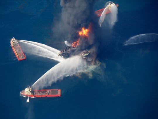 FILE - In this April 21, 2010, aerial file photo, the Deepwater Horizon oil rig burns in the Gulf of Mexico, more than 50 miles southeast of Venice on Louisiana's tip. Environmental activists Karen Savage and Cherri Foytlin wrote an article criticizing a company that published a study finding no connection between chemicals released by the explosion and health problems reported by some cleanup workers. Massachusetts' highest court will hear arguments Oct. 7, 2016, in a bid by Savage and Foytlin to throw out a defamation lawsuit filed by the company, siting a state law that protects citizens exercising their free speech rights. (AP Photo/Gerald Herbert, File)