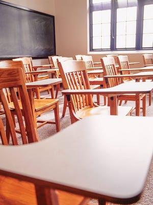 Desks arranged in an empty classroom before COVID-19 brought about the need for social distancing.