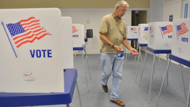 Precinct worker Peter Sonbert helps set up the voting booths on Aug. 14, 2012, before the polls open in Jupiter.