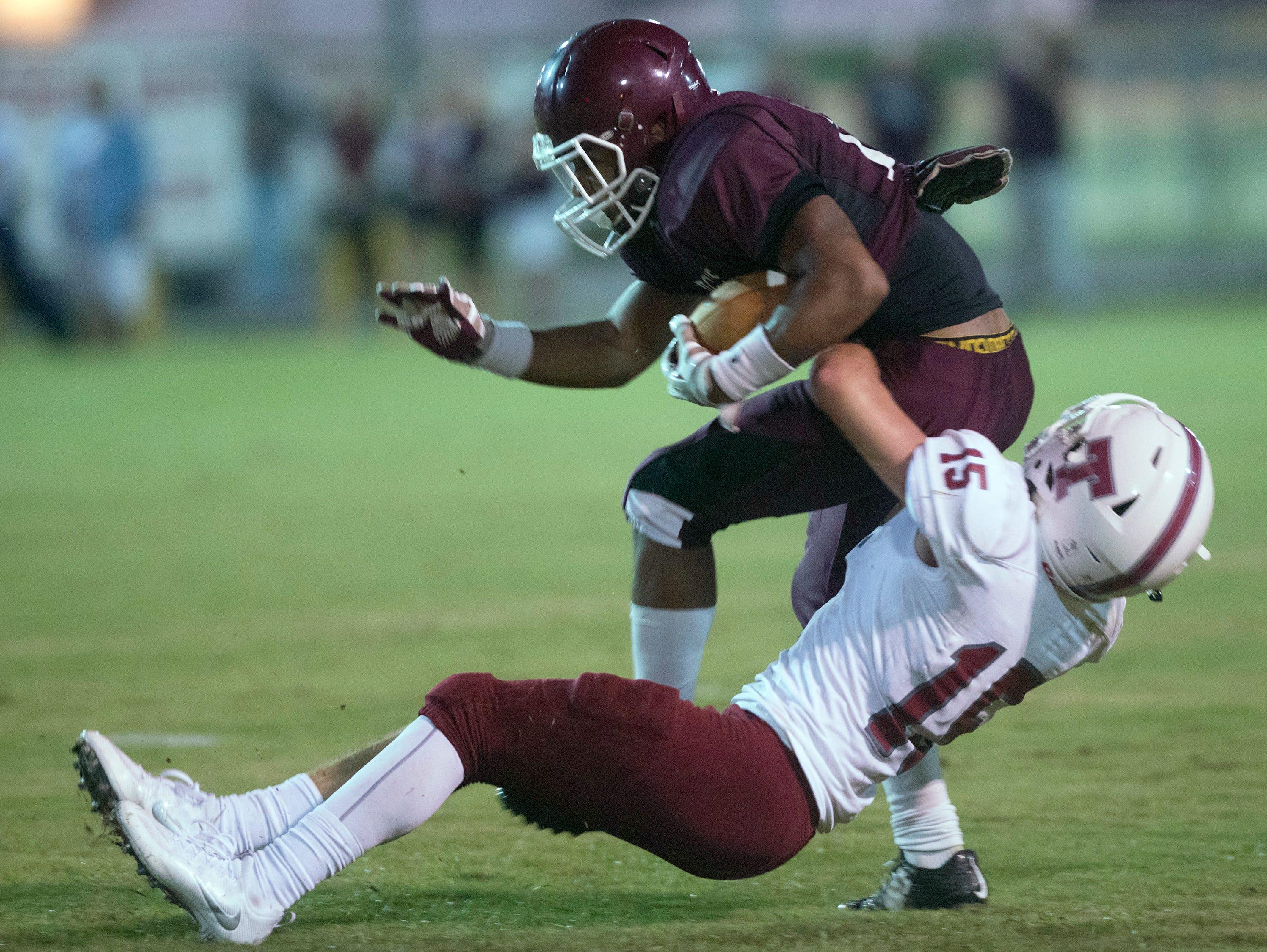 Tate High School safety, Reid Halfacre, (No. 15) wraps up Pensacola High School wide receiver, Freddie Hughley, (No. 13) during Friday night's preseason opener.