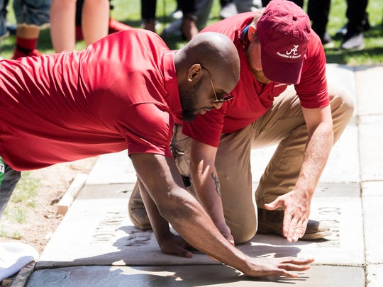 Rashaan Evans puts his hands in cement during the Walk of Fame Ceremony at Denny Chimes on the University of Alabama campus in Tuscaloosa, Ala. on Saturday April 21, 2018.