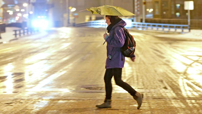 A woman crosses a slushy W. State St. at N. Old World Third St. in Milwaukee on Tuesday morning.  It's a sloppy mess out there this morning, as light sleet and freezing rain are falling on top of the inch or two of snow that fell last night to create slippery road conditions in the Milwaukee area and across southern Wisconsin.