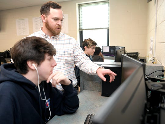 Centennial High School teacher Stephen Huff helps Nathan Blair with a coding assignment during class Feb. 21, 2018. Huff, 31, has stage 4 lung cancer.