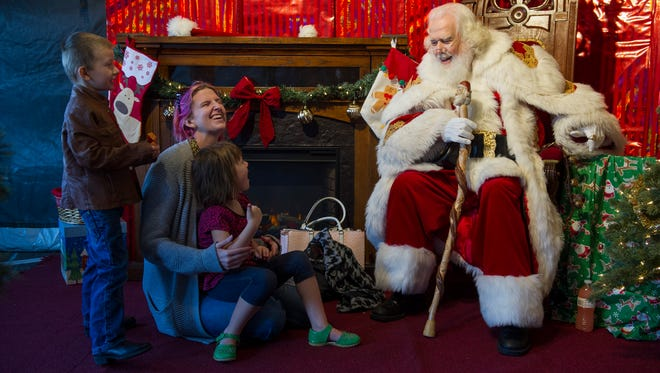 Danielle Veirs, of Evansville, sits with her children, Teddy Veirs, 4, and Heidi Veirs, 4, as they joke with Santa Claus, portrayed by David Belcher, also of Evansville, during the 8th annual 911 Gives Hope toy drive in Evansville, Friday, Dec. 2. 2016. Toys, clothes and other items collected will be donated to children spending the holidays in area hospitals.
