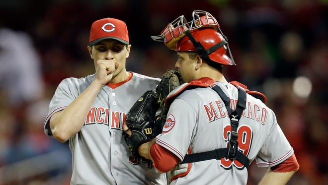 Cincinnati Reds starting pitcher Homer Bailey, left, and catcher Devin Mesoraco talk on the mound during the third inning of a baseball game against the St. Louis Cardinals, April 8, 2014, in St. Louis.