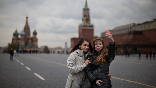 """Two women pose for a selfie on Red Square with St. Basil's Cathedral, left, and the Spasskaya Tower, right in Moscow in this file photo from Oct. 6, 2014. Alarmed by the number of Russians who have been killed while taking photos of themselves with smartphones, Russian police have started a new campaign called """"Safe Selfies."""" The instructions issued Tuesday, July 7, 2015, warn against standing on railroad tracks, climbing onto roofs or posing with a gun or a tiger."""