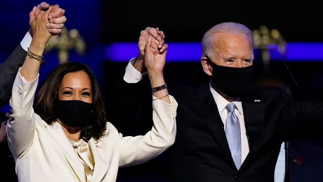Vice President-elect Kamala Harris holds hands with President-elect Joe Biden and her husband Doug Emhoff as they celebrate Saturday, Nov. 7, 2020, in Wilmington, Del.