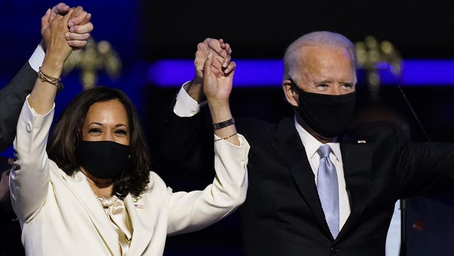 FILE - In this Nov. 7, 2020, file photo Vice President-elect Kamala Harris holds hands with President-elect Joe Biden and her husband Doug Emhoff as they celebrate in Wilmington, Del. Black policy leaders will play a pivotal role in President-elect Joe Biden's transition team, marking one of the most diverse presidential agency review teams in history.