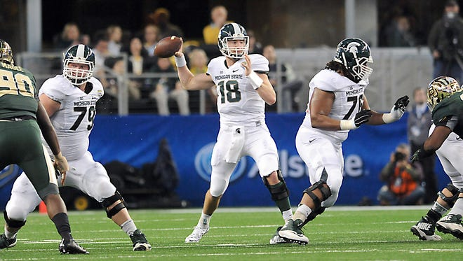 MSU quarterback Connor Cook gets protection from Kodi Kieler, left, and Donavon Clark, right, as he passes against Baylor in the Goodyear Cotton Bowl Classic at AT & T Stadium in Arlington, TX, on Jan. 1, 2015. Kieler was injured during the game against Oregon.