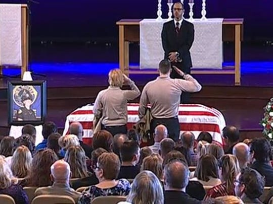 Officers salute the casket of fallen Des Moines police