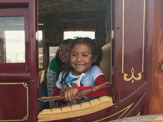 Children get a firsthand look inside a stagecoach during Christmas at Old Fort Concho.