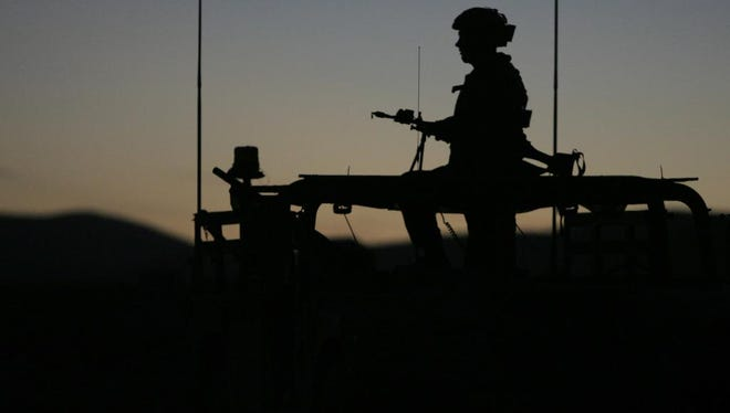 A soldier from Charlie Battery of the 2nd Battalion 222nd Field Artillery stands watch with his SAW machine gun atop a Humvee over the town of Medina Wasl in Fort Irwin in California.
