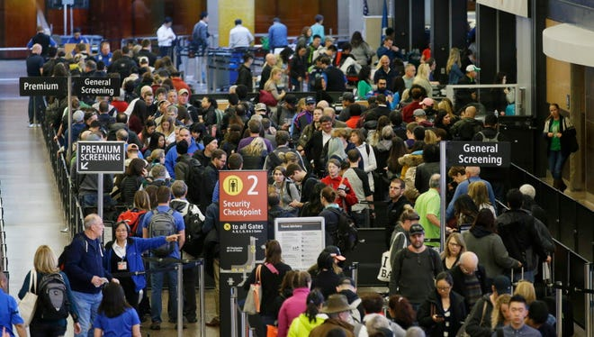 Travelers wait in line March 17, 2016, for security screening at Seattle-Tacoma International Airport in Seattle.