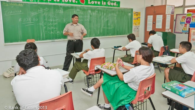 In this April 2013 file photo, Bank of Guam staff and others share knowledge with students during National Teach Children to Save Day at San Vicente Catholic School in Barrigada.
