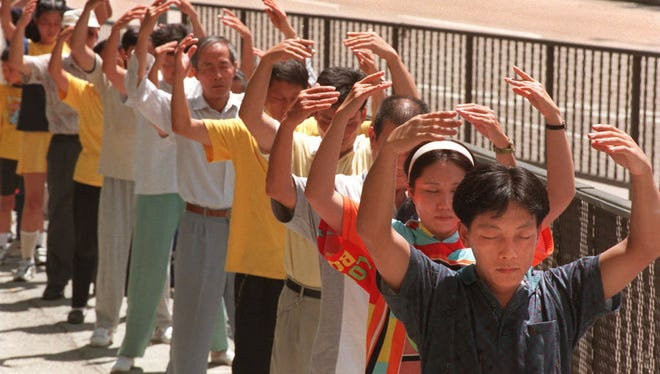Followers of the popular meditation group Falun Gong do their exercise outside the mainland Chinese-run Xinhua News Agency office in Hong Kong in this file photo.