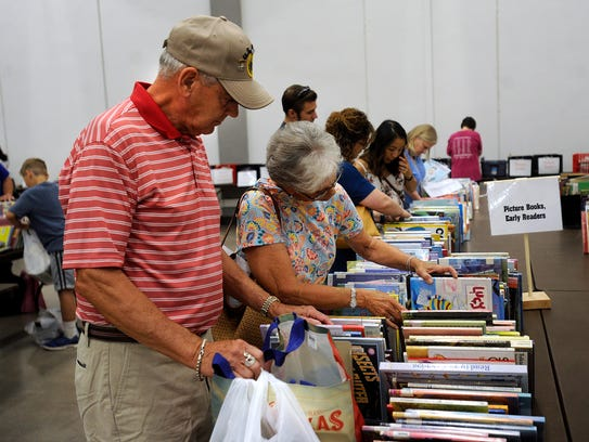 Book buyers look through children's books on sale at