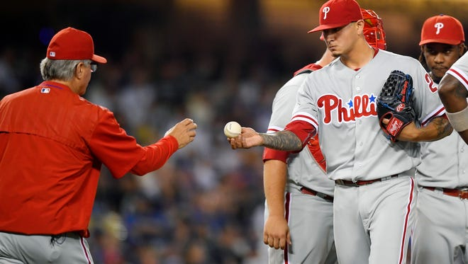Philadelphia Phillies starting pitcher Vince Velasquez, right, hands the baseball to manager Pete Mackanin as he is taken out of the game during the fifth inning Tuesday against the Los Angeles Dodgers.