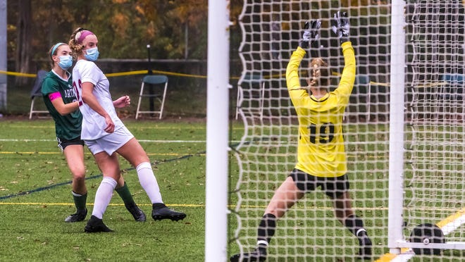 Kyleigh Wheaton watches her shot go past Bishop Stang's Bridget Markey to tie up the game at 1-1.