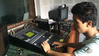 One of the team members of Good News FM Radio in Nepal at the console of their new digital mixer.