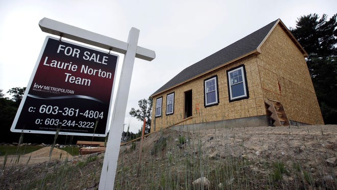A for sale sign is displayed in front of home under construction in Raymond, N.H. On Monday, June 25, the Commerce Department reports on sales of new homes in May.