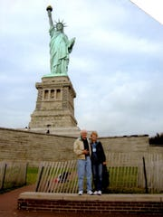Harold and Marilyn Salzl Brinkman stand in front of the Statue of Liberty while it was under repair in2010.