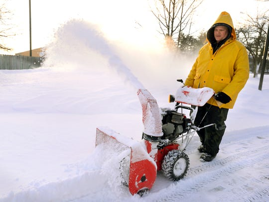 Matt Clark gets an early start clearing the snow at the Somerset Senior Community in Lansing Monday after the area's heavy snowstorms.