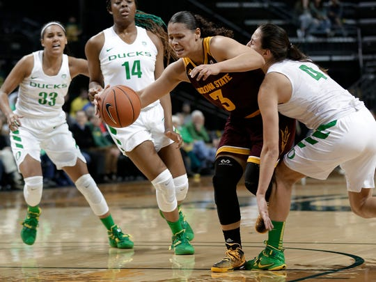 Arizona State's Sabrina Haines, middle, dribbles past Oregon's Maite Cazorla, right, Jillian Alleyne (14) and Lexi Petersen, left, during the first half of an NCAA college basketball game Friday, Jan. 29, 2016, in Eugene, Ore.