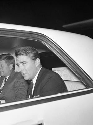 John F. Kennedy, President-elect in car after his arrival on Jan. 11, 1961 in West Palm Beach, Florida from Washington on right is his brother-in-law Peter Lawford who accompanied the President-elect from the nation's capital. Mr. Kennedy with a busy schedule ahead hoped to get in some work on the inaugural address he will deliver on January 20. (AP Photo)