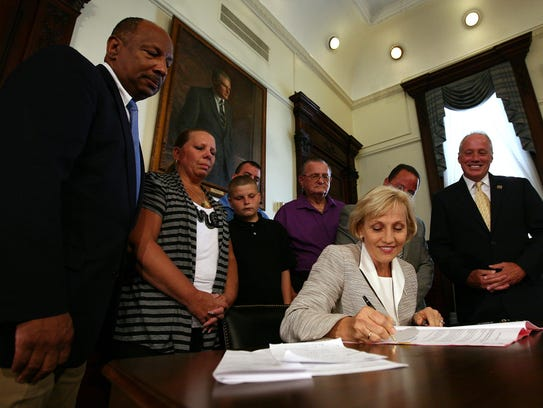 Lt. Gov. Kim Guadagno signs Fred Baker's Law, which
