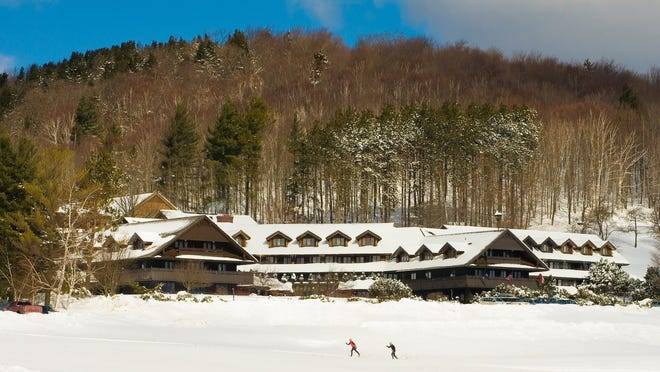 A pair of cross-country skiers in front of the Trapp Family Lodge in Stowe.