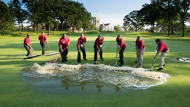 Workers attempt to remove water from a fairway at Olympia Fields Country Club prior to the start of Tuesday's second round a the U.S. Amateur.