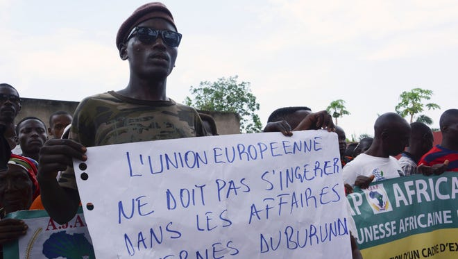 """A demonstrator holds a placard reading """"The European Union must not interfere in Burundian home affairs"""" as people protest against the European Union, the International Criminal Court and the Resolution against Burundi in Bujumbura on Oct. 8, 2016."""