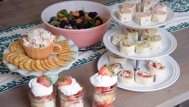 A bridal tea party spread: Smoked salmon dip, spinach salad with fruit. tortilla pinwheels and strawberry shortcake in jars.