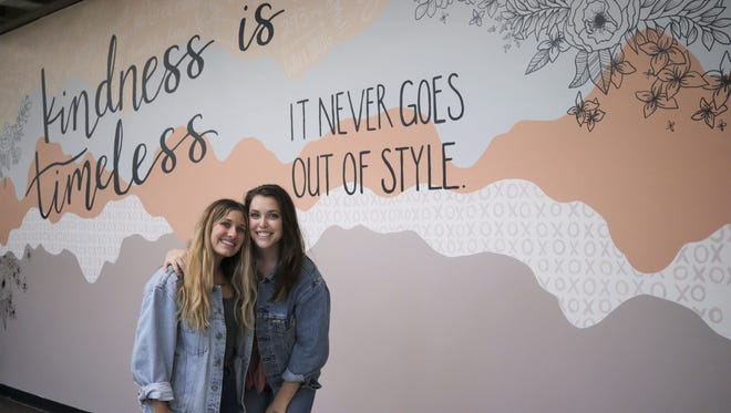 Sarah Nelson (left) and Rebekah Rinehart pose for a photograph in front of their new mural in the Empire Mall food court July 29, 2018, in Sioux Falls, SD.