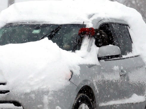 A commuter checks his wiper blades in snowy Chicago on Thursday.
