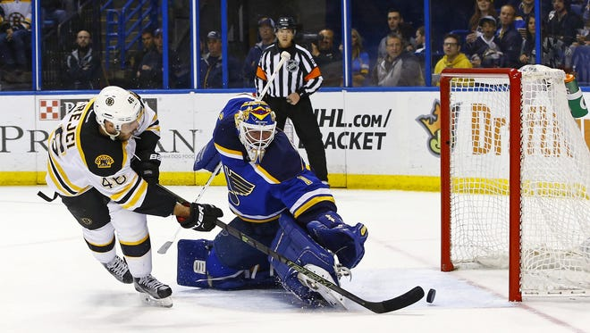 Boston's David Krejci, left, scores a goal against Blues goalie Brian Elliott during the first period of Friday night's game in St. Louis.