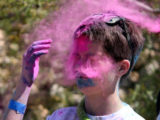 Acey Hokit dispels the last of her dust into her face after the 5K fun run Saturday at Voiers' Pit Park.