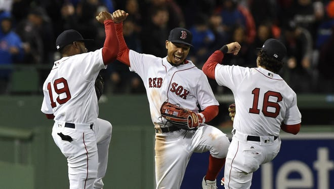 Boston Red Sox outfielders   Jackie Bradley Jr. (19), Mookie Betts (center) and Andrew Benintendi (16) react after defeating the Chicago Cubs.
