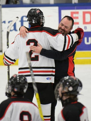 Churchill head coach Jason Reynolds give Josh Friend a hug after the Chargers beat Gabriel Richard in the Div. 3 state semifinl game.