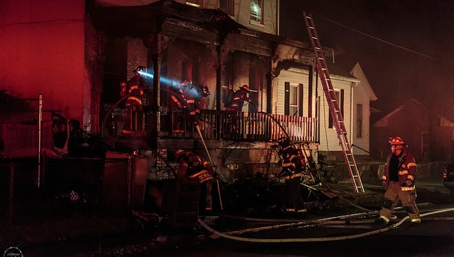 Chillicothe firefighters work to douse hot spots from a fire at 36 1/2 W. Sixth St., on Feb. 17, 2017.